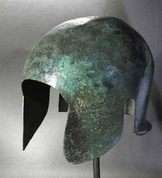 Extremely rare, a Greek Illyro/Chalcidian bronze helmet displays aspects that indicate it was captured at war, then modified by the enemy to suit their own specifications. Originally, it was Corinthian in style, with big ear flaps and a nose cover. Later, it was made to look more Illyrian.