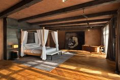 """Master bedroom with old oak beams and a sheet iron backdrop to the bed in this…"