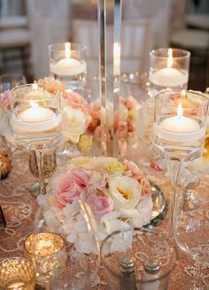 White Floating Candles Are Placed In Tall Gl Standatched By Metallic Vases Holding Pink And Flowers