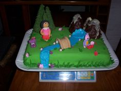 Dora the Explorer - The trees maked with ice cream cones and royal icing; the water in royal icing; the mountains in chocolate Black and White; Dora, Boots and Pack in modelating Paste and Gumpaste; the rest of the Cake in gump0aste andRoyal Icing; to be rolling in rolled fondant green.