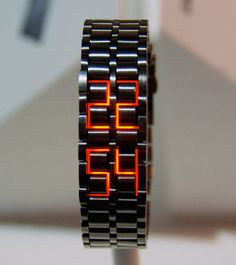 "Fashionable unisex bracelet watch that tells time with LEDs built into the stainless steel bands.  Blending seamlessly into the watch's stainless steel links, the four disguised LED sets are only detected when they illuminate to form 9/16"" H red digital numbers at the press of a button.  The ..."