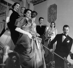 Charles James standing on steps with models wearing dresses from his collection in the 1950s. Credit Eliot Elisofon/The LIFE Picture Collect...