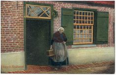 Boerin in klederdracht bij de voordeur. Rechts langs het bovenlicht van de deur een palmtak - 1900