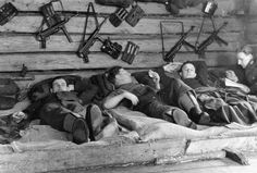 German troops resting. Note their MP40 submachine guns and spare magazines on the wall.