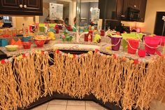 hawaiian party- this is a pretty simple and cost effective way to decorate for a luau party – grass skirts and sand buckets from the dollar store- use the shovels as the spoons….  kids would probably even have fun cleaning up after by spraying out the b