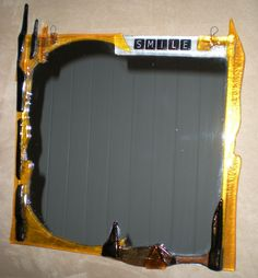 """Fused glass mirror. There was a strange empty spot on top so I wrote """"smile."""""""