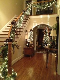 I sooo want a big open plan stair case with a fab banister so I can decorate it like this every Christmas lol