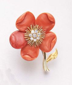 AN ELEGANT CORAL AND DIAMOND FLOWER BROOCH, BY VAN CLEEF & ARPELS**   With undulating coral petals centering upon a gold wirework and circular-cut diamond cluster pistil, extending a polished gold stem and leaf, mounted in 18k gold, with French assay marks and maker's marks  Signed VCA for Van Cleef & Arpels, Made in France, no. 1V844.50  With maker's marks for Van Cleef & Arpels