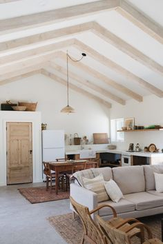 I absolutely love this open floor plan- the neutral rustic kitchen, high ceilings, white walls and wood. It's my perfect room