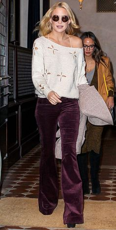 Kate Hudson channels Penny Lane IRL in burgundy velvet flare pants by J Brand, a flower cutout sweater, and round sunglasses