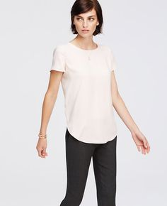 Teeing up: topping our list of A-list essentials, our dressy tee keeps it pretty in fall's most wanted hues. Jewel neck. Short sleeves. Shirttail hem.
