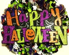 Happy Halloween Fabric Wreath with sign!  Dress up your front door or wall with this handmade fabric rag wreath.  This features Halloween colors (purples, oranges, greens, whites) in addition is a little decor with a sign saying Happy Halloween (which is easily removable)