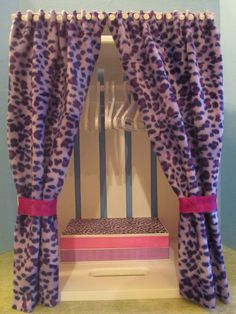 DIY closet for American Girl Doll clothes.  Take your basic crate found at most craft stores, paint and stand on it's side.  Add a dowel for a rod (make sure your hanger fits on it).  Add funky fabric for the doors and attach it with thumb tacks.  Ribbon was used for the tie backs and a cardboard box was decorated for fancy shoe storage.  Add drawer pulls to sides for accessories if desired.