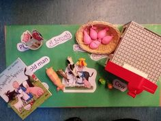 Squash and a squeeze story table, including small world figures, duplo farm house, lollipop stick picture puppets and squash and squeeze sensory balloons filled with rice, playdough, flour, salt and lentils the children love these!
