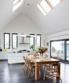 Large vaulted ceilings and multiple windows can make a room feel larger than it actually is. If you're decorating a primarily white-and-black space, bring in an unexpected piece of wood furniture to warm it up and give it personality. #design #kitchen