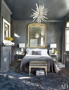 Though Lee Ledbetter was asked to decorate a New Orleans real-estate tycoon's historic home in black and white, the architect-designer smuggled in other neutrals to break up the stark palette. Silvery grays cover the ceiling, walls, fireplace, and floor of a guest room. The starburst chandelier and mirror over the bed give the room a breezy glamour | archdigest.com