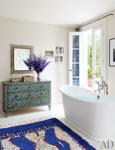 The master bath is appointed with an antique painted chest and a rug from François Gilles Carpets | archdigest.com