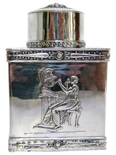 Hanau Silver (800) Neoclassical Tea Caddy This is a lovely 800 Hanau silver tea caddy, made in Germany in the 1890s. It has a distinctive Neo-Classical design to it and emanates a regal air. The two larger sides feature the same embossed image of a woman, dressed in flowing draped attire, carving the bust of a Trojan warrior.