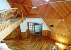 Upper level geodesic dome house, Main entrance, oak floor, wood wall,  wall light fixture, natural wood rails, skylight,  home for sale, 9121 CR 23 Brainerd MN 56401 Geodesic Dome Homes, Wall Light Fixtures, Dome House, Main Entrance, Ceiling Height, Skylight, Solar Panels, Wood Wall, Natural Wood