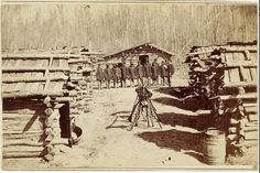 A group of soldiers from the 64th USCT pose next to their cabins at Davis Bend, south of Vicksburg