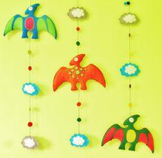 móbile composto por 1 pterodáctilo grande de 30 cm de envergadura, de cores diversas, com 3 nuvens, costurado e bordado à mão <br> <br> <br>70 x 30