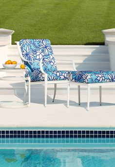 love the fabric on the chair. also like the combo of aqua and navy blue tiles on the pool, and the crisp white patio