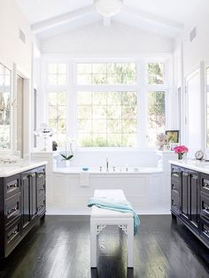 Dark cabinets and floors provide contrast for the white countertops and trim ~ Love the windows that allow natural light to illuminate the high ceiling
