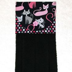 Always have a towel at the ready with this handmade hanging towel. Featuring a designer fabric of retro pink and gray cats on black and a coordinating fabric in a glittery polka dot pattern, it is sure to add fun to your kitchen. The plush terry towel is more luxurious than a standard kitchen towel. This item works well buttoned over the handle of stove or dishwasher. It can even be used over a towel bar in the bathroom or powder room.  6 x 17.5 when hanging. The front of this hanging towel…