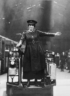 A female trolley driver signals a left turn on a platform at Liverpool Street Station, London, WW1