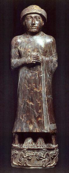 Escultura de Gudea de Lagash (¿su hijo Ur-Ningirsu?). Período Neosumerio. Sobre un pedestal tallado y con relieves de significación religiosa.