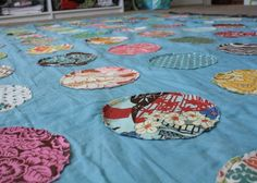 """Awesome circle quilt.  So much scrappy color in this!  She layered 6"""" circles over a sheet and sewed them all down.  Then she added batting, a back, and ran through the sewing machine, sewing again around half of the circles to quilt together.  Love the colors!"""