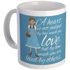 A heart is not judged by how much you love, but by how much you are loved by others. Beautiful Wizard of Oz quote next to a cute Dorothy picture on a pretty blue mug.