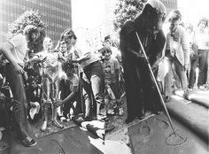 Fans descend on Mann's Chinese Theatre in Hollywood to witness Darth Vader, C-3PO and R2-D2 immortalizing their footprints in wet cement in the theater's forecourt (1977)