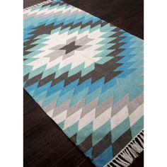 Bring the heat of the Southwest to your flooring with this handsome flat-woven rug. Turquoise tones and a touch of fringe give it that Santa Fe flair for any space.
