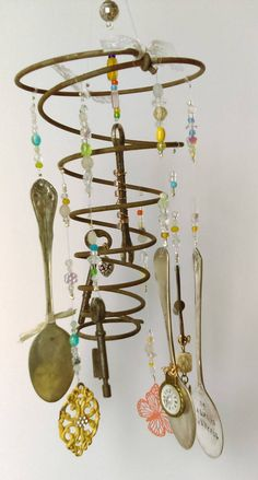 A unique wind chime made from a vintage bed spring with sparkly beads, old keys, charms, a tiny wrench and spoons. Two of the spoons are hand stamped Find Joy and Be Always Thankful. It hangs 15 long and will look lovely hanging on your front porch