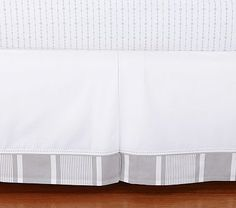 pattern for crib skirt - off white/linen with patterned trim and visible stitching.