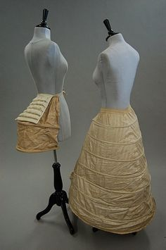 RIGHT A cotton crinoline frame, circa 1870, flat in front and with nine metal bands, elasticated inner bands; together with a white horsehair bustle c.1870; LEFT and a coarse white calico bustle or half pannier - fancy dress,