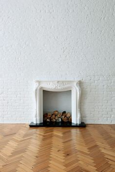 parquet flooring, white brick wall, antique solid white fire place.
