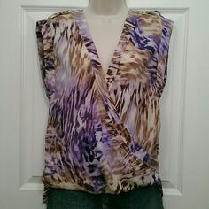JLo wrap-style oversized sleeveless top Pretty animal print top features a wrap-style look on the front (not adjustable). Normal length in front, lower in the back. Size XS but runs really oversized. Would work well as a Medium. No flaws that I can find.  See the current Sale Ad at the top of my closet ⭐ Bundle & Save ⭐ or Make an offer! Jennifer Lopez Tops