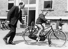 De eerste fietsrijles. De fiets werd  'op de groei...' gekocht: blokken op de trappers!