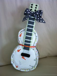 Diaper Guitar. So very adorable for a baby shower, especially if one of the parents play the guitar or another musical instrument! Other creative diaper arrangements are here: http://mybellapearlgifts.com/horse-and-carriage-gift-baskets/