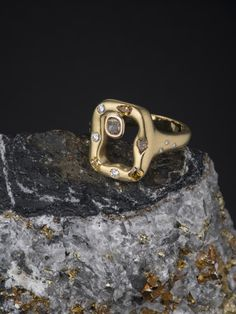 I love how this rectangular-shaped Émeraude ring is perched on a gem-flecked rough stone, to reflect the beautiful natural origins of gemstones. I can hand-make this piece in 18K yellow, green, or rose gold. It features a large cognac-colored diamond in the center and then I sprinkle random various other smaller colored diamonds in different shapes along its frame. Just for contrast, I use full-cut white diamonds as well, gypsy-set on the frame and on the band.