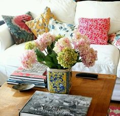 Fake hydrangeas in a colourful square vase A coffee table with a selection of Taschen books (Degas, Van Gogh, etc), other art books/comics, and good magazine titles like Monocle and Foreign Policy :) With cushions of multiple patterns and designs.