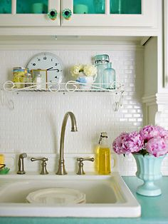 Seriously, LOOK how cheerful this kitchen feels... is just the sink area!!! If u can make me feel that happy in front of a sink just imagine the REST of it!! For those of us getting tired of white subway tile but still crave the versatility, heres A great alternative... Mini Subway Tile!! Perfect for small kitchen spaces!! plus i love the turquoise blue cabinet glass, the vintage glass knobs, colorful blue countertop