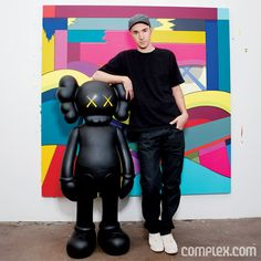 KAWS: Kaws in front of his painting, with his sculpture toy.