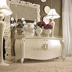 _ Lord wooden sideboard in white crackle finish, cat. B, Prince decoration and tassels<br> _ Prince mirror in snow finish, cat. B, aged mirror<br> _ Operà wooden floor lamp in snow finish, cat. B, lampshade in Pongè 5 fabric, cat. A<br> _ Operà wooden table lamps in snow finish, cat. B, lampshades in Pongè 5 fabric, cat. A