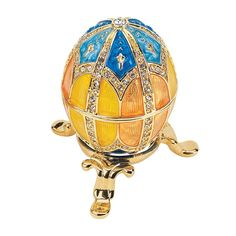 It's impossible to leave this gorgeous enameled egg alone! Lifting this collectible beauty from its petite tripod base, examining its apricot-hued enamel and rotating it towards the light to admire it
