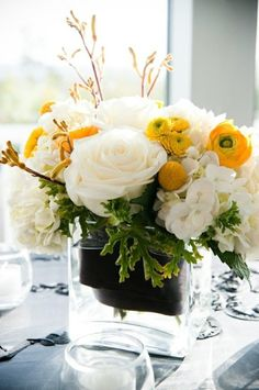 white ranunculus, white roses, yellow flowers centerpiece