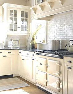 Combine cream cabinets and aga with white backsplash