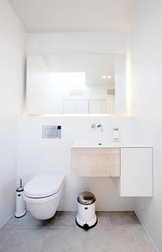 Badeværelset er komprimeret, uden at det virker mast. Spejlet er lavet med et par lysrør på bagsiden, som kaster lys hele vejen rundt langs spejlet. Det giver et godt spejllys, der ikke kaster skygger i ansigtet. Håndvaskens front er lavet af planker fra Dinesen samt et tilpasset køkkenelement fra HTH. Toilettet Starck 3 er fra Duravit, og affaldsspand, toiletbørste og sæbedispenser fra Vipp.